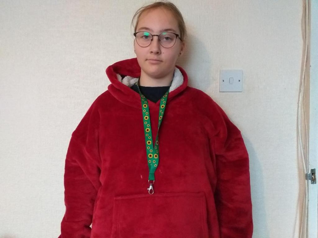 The picture shows a girl. She is wearing a red hoodie. She is also wearing a sunflower lanyard